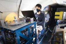 A young man wearing a face mask sits behind a monitor, surrounded by technology on a plane.