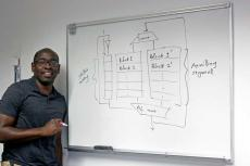 Tosiron Adegbija stands at a whiteboard with a diagram of computer memory caching written on it in black marker