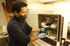 Suchol Savagatrup, wearing a face masks and blue latex gloves, reaches into a cabinet in his lab.