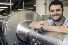 Alex Craig smiles and rests his arm on a 104-foot silver wind tunnel