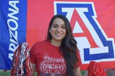Maira Garcia smiles and holds two pom poms. Behind her is the University of Arizona Block A logo.