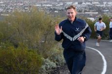Ryan Raettig smiling and waving as he runs up Tumamoc Hill.