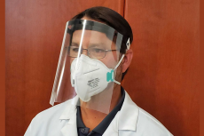 Man wearing a plastic face shield and a white lab coat